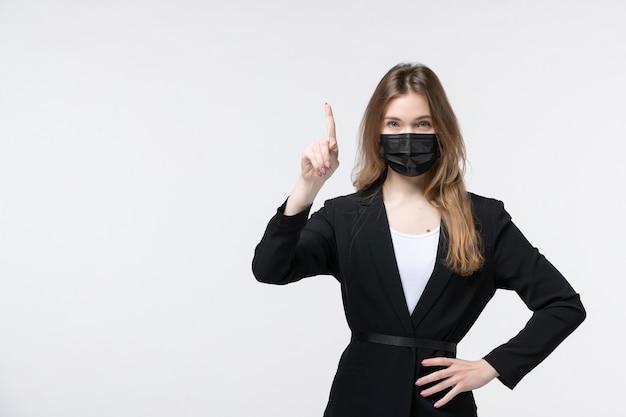 サージカルマスクを着用し、白を上向きにスーツを着た若い女性の正面図
