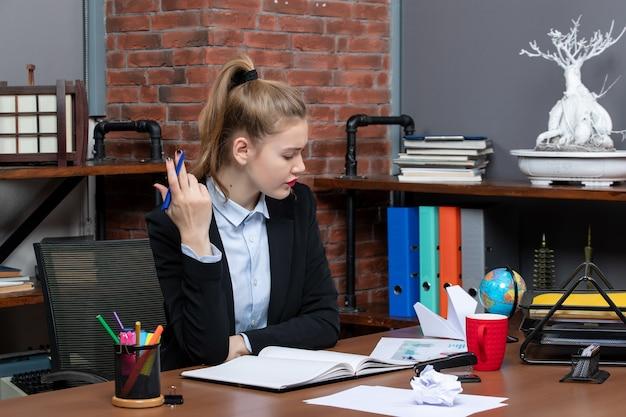 테이블에 앉아 사무실에서 신중하게 무언가에 집중하는 젊은 여성의 전면 보기