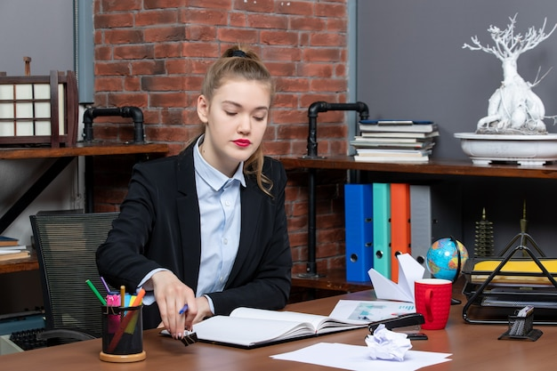 テーブルに座って、オフィスのノートで彼女のメモを読んでいる若い女性の正面図