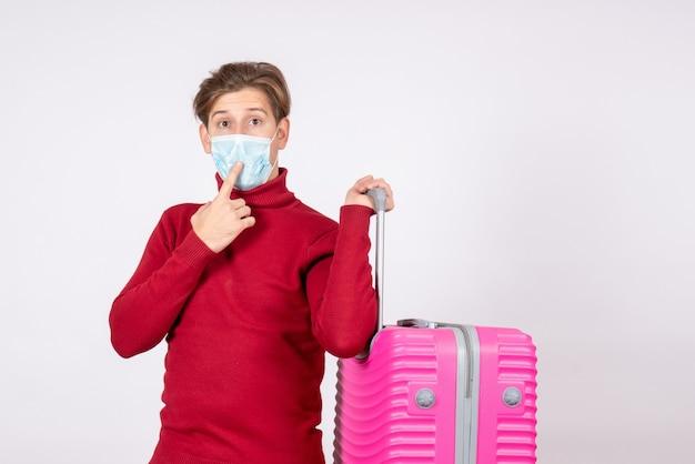 흰 벽에 분홍색 가방을 들고 젊은 남성의 전면보기