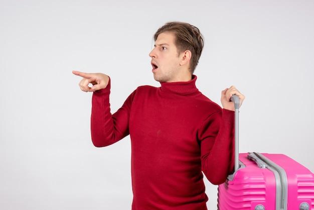 Вид спереди молодого мужчины, несущего розовую сумку на белой стене