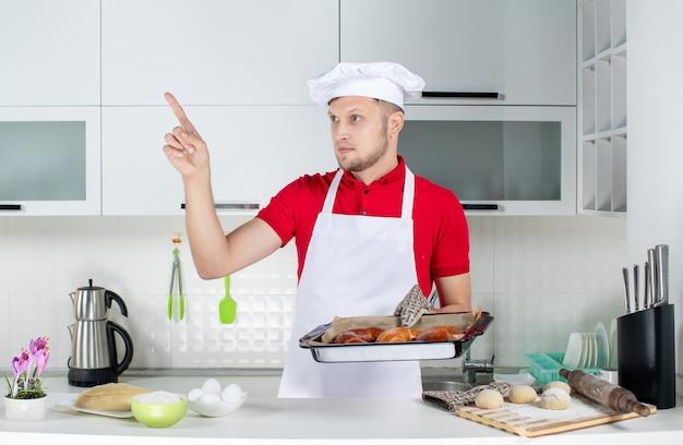 焼きたてのペストリーを持ち、白いキッチンを指差すホルダーを着た若い男性シェフの正面図