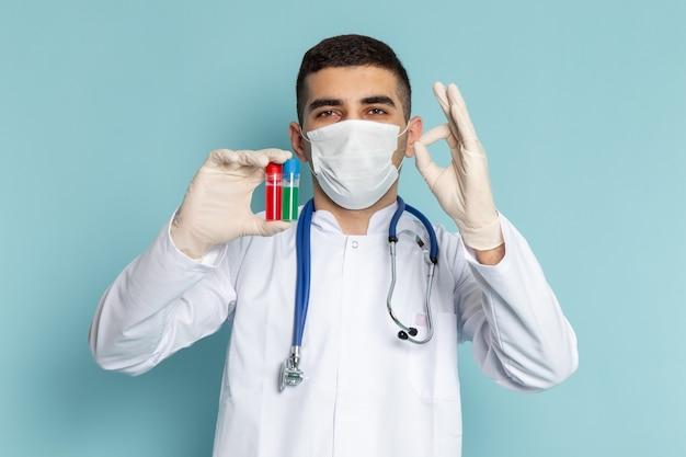 마스크와 플라스크를 들고 파란색 청진기와 흰색 정장에 젊은 남성 의사의 전면보기