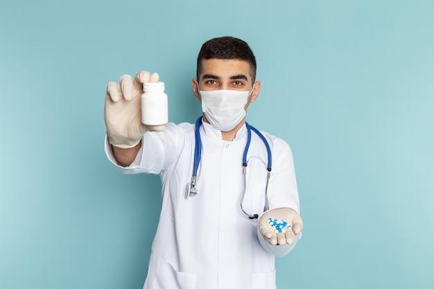 薬を保持している青い聴診器で白いスーツの若い男性医師の正面図