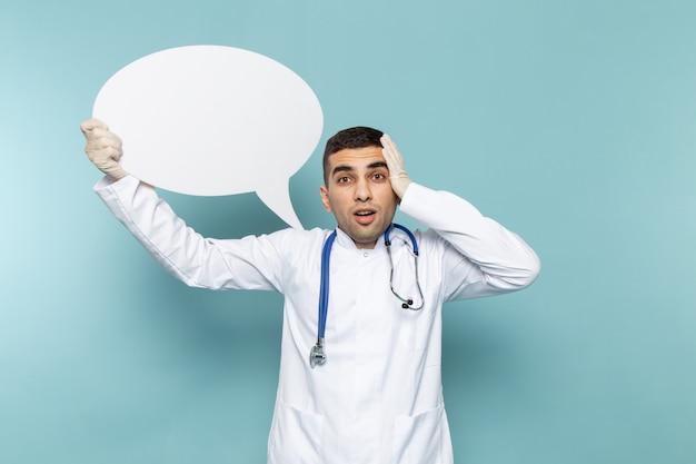 Вид спереди молодого мужчины-врача в белом костюме с синим стетоскопом с белым знаком