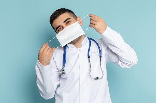 身に着けているマスクを笑顔青い聴診器で白いスーツの若い男性医師の正面図
