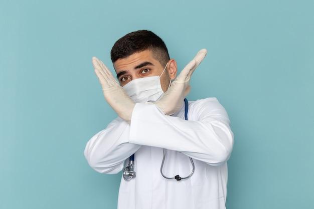 滅菌マスクを身に着けている青い聴診器で白いスーツの若い男性医師の正面図
