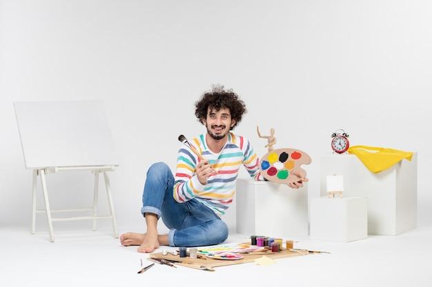 흰 벽에 그림을 그리는 젊은 남성의 전면 모습
