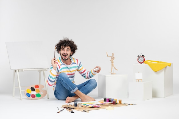 白い壁にペンキで絵を描く若い男性の正面図