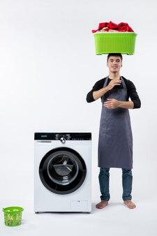 Вид спереди молодого мужчины, складывающего грязную одежду на белой стене