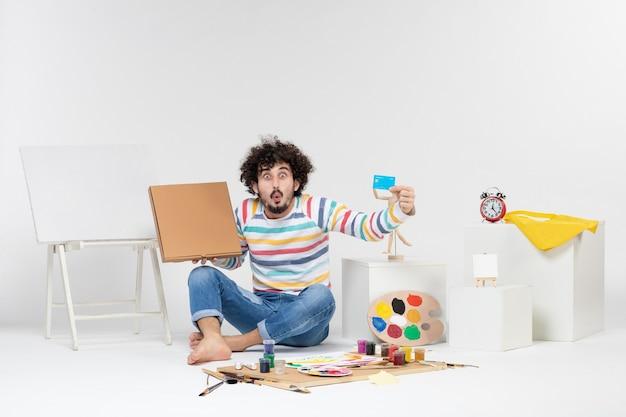 白い壁に銀行カードとピザボックスを保持している若い男性の正面図