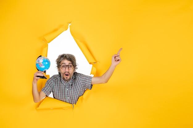 Вид спереди молодого мужчины, держащего земной шар на желтой стене