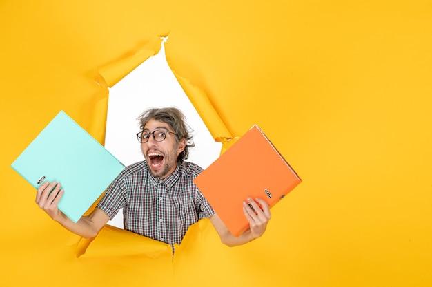 黄色の壁にファイルを保持している若い男性の正面図