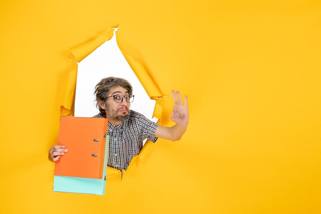 노란 벽에 파일을 들고 있는 젊은 남성의 전면 모습