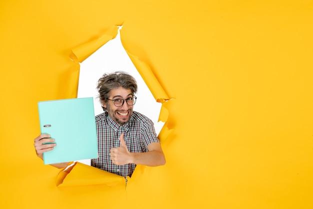 노란색 벽에 녹색 파일을 들고 있는 젊은 남성의 전면 모습