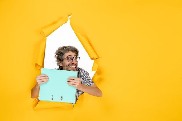 黄色の壁に緑のファイルを保持している若い男性の正面図