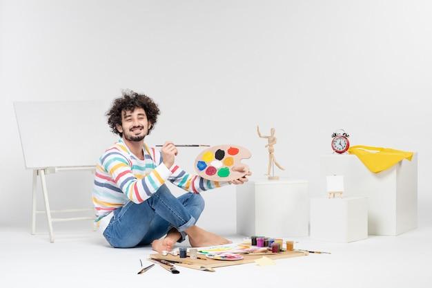白い壁に描くための塗料とタッセルを保持している若い男性の正面図