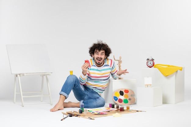 흰 벽에 작은 캔 안에 그림을 그리기 위해 페인트를 들고 있는 젊은 남성의 전면
