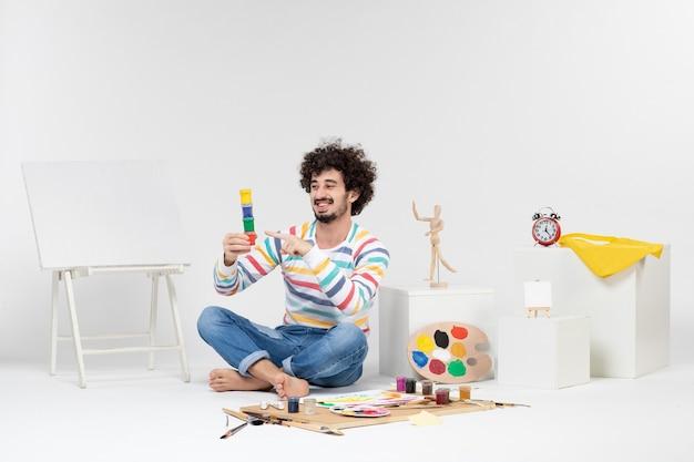 白い壁の小さな缶の中に描くための塗料を保持している若い男性の正面図
