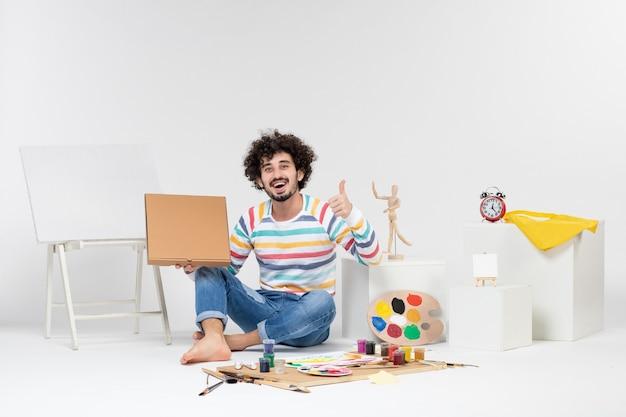 白い壁にピザボックスを保持している若い男性の正面図