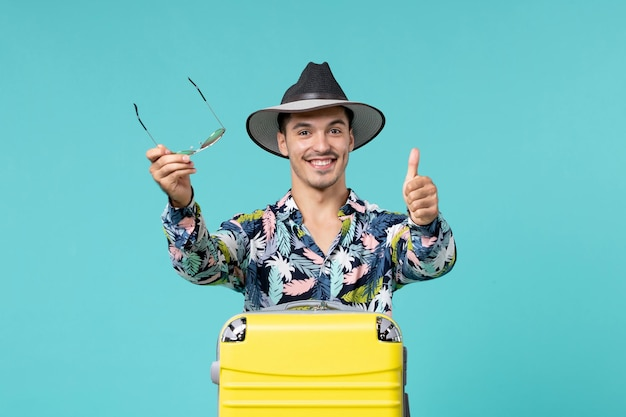 サングラスを保持し、水色の壁で旅行の準備をしている若い男性の正面図
