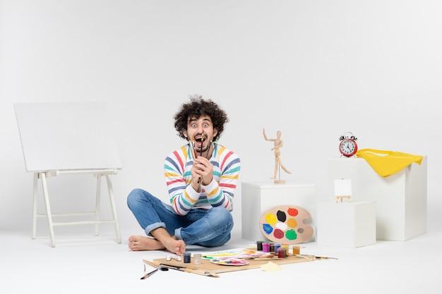흰 벽에 그림을 그리기 위해 술을 들고 있는 젊은 남성의 전면 모습