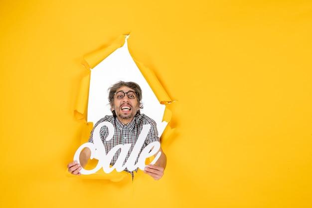 黄色の壁に白い販売を保持している若い男性の正面図