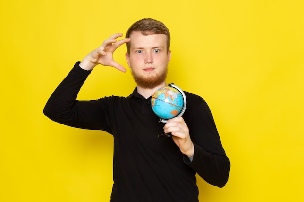 Вид спереди молодого мужчины в черной рубашке держит маленький глобус