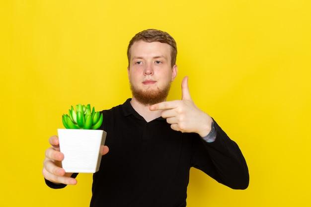 작은 녹색 식물을 들고 검은 셔츠에 젊은 남자의 전면보기