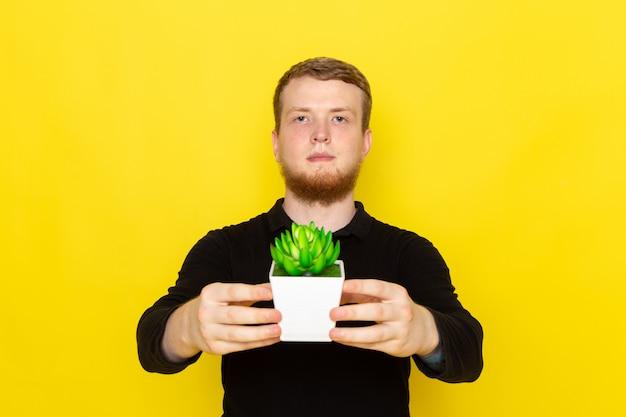 小さな植物を保持している黒いシャツの若い男性の正面図