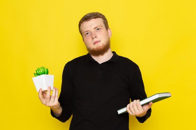 植物とコピーブックを保持している黒いシャツの若い男性の正面図