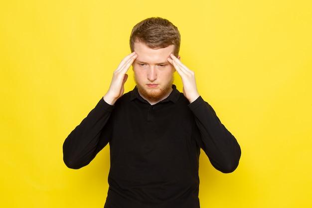 ポーズと頭痛を持っている黒いシャツの若い男性の正面図