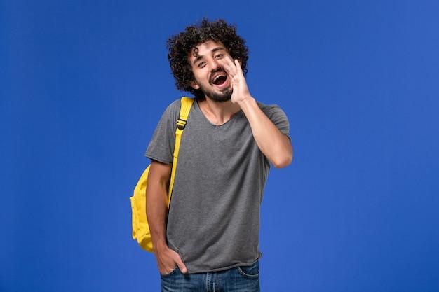 青い壁に誰かを呼び出す黄色のバックパックを身に着けている灰色のtシャツの若い男性の正面図
