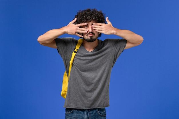 青い壁に目を覆っている黄色のバックパックを身に着けている灰色のtシャツの若い男性の正面図
