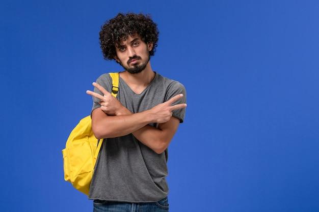 青い壁にポーズをとるだけで黄色のバックパックを身に着けている灰色のtシャツの若い男性の正面図