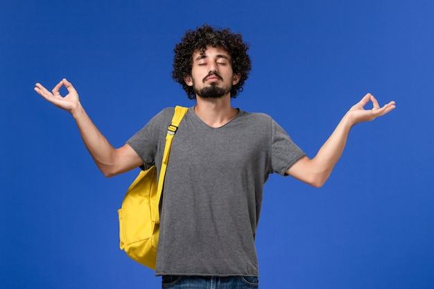 青い壁で瞑想する黄色のバックパックを身に着けている灰色のtシャツの若い男性の正面図