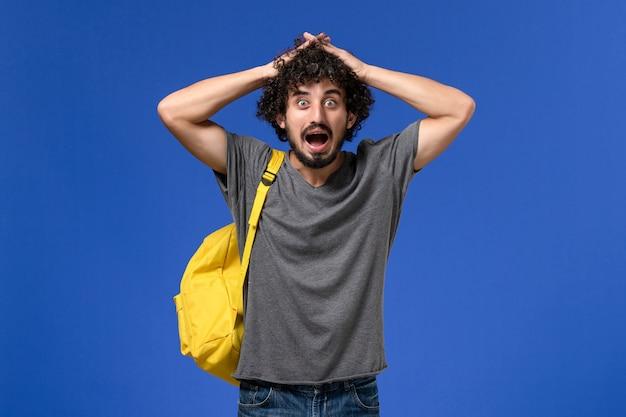 파란색 벽에 노란색 배낭을 입고 회색 티셔츠에 젊은 남성의 전면보기