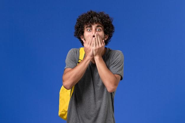 파란색 벽에 충격을받은 표정으로 포즈를 취하는 노란색 배낭을 착용하는 회색 티셔츠에 젊은 남성의 전면보기