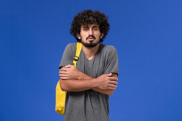 Вид спереди молодого мужчины в серой футболке с желтым рюкзаком, дрожащего на синей стене
