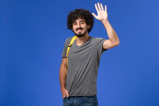 Вид спереди молодого мужчины в серой футболке с желтым рюкзаком, улыбающегося и машущего на синей стене