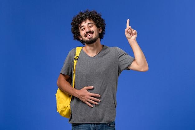 Вид спереди молодого мужчины в серой футболке с желтым рюкзаком, улыбающегося на синей стене