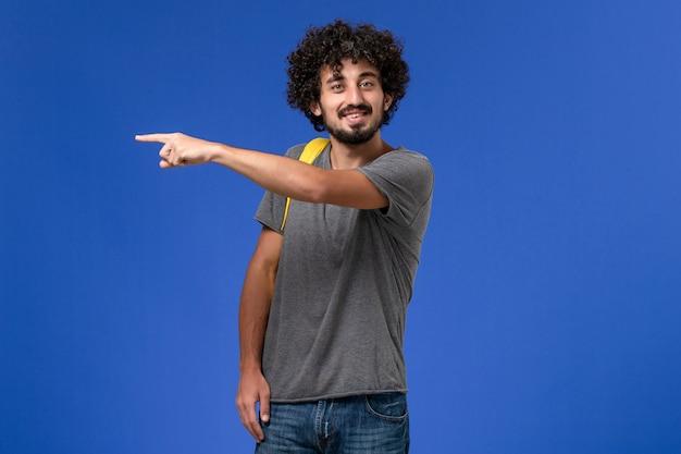 青い壁に笑みを浮かべて黄色のバックパックを身に着けている灰色のtシャツの若い男性の正面図