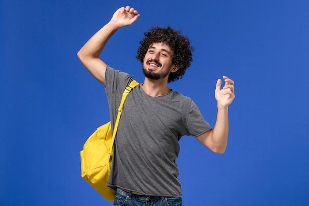 파란색 벽에 웃 고 노란색 배낭을 입고 회색 티셔츠에 젊은 남성의 전면보기