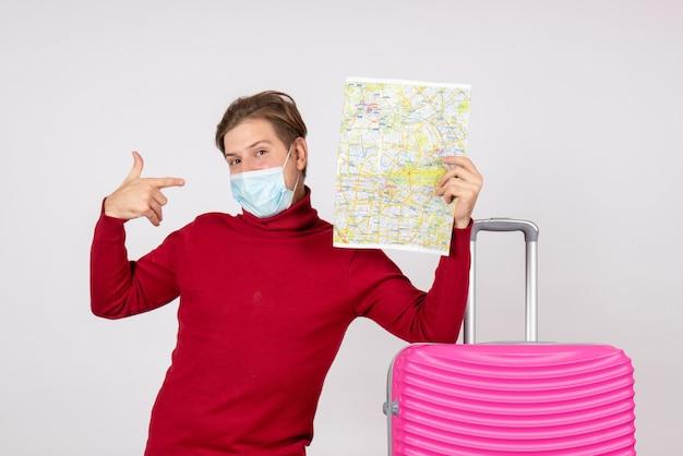 白い壁に都市地図を保持しているマスクの若い男性の正面図