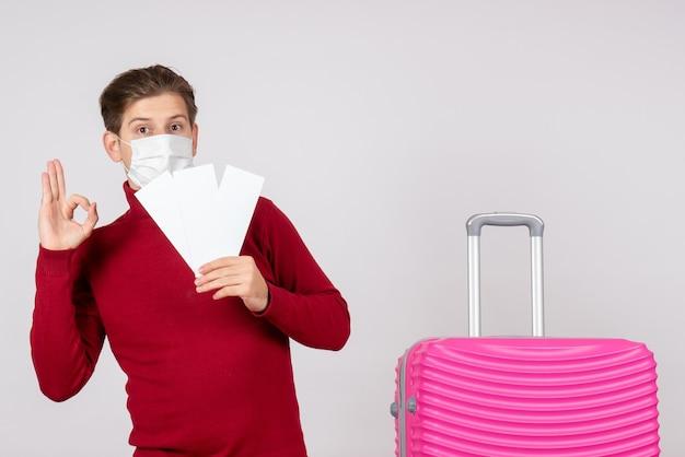 白い壁に飛行機のチケットを保持しているマスクの若い男性の正面図