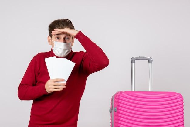 Вид спереди молодого мужчины в маске, держащего билеты на самолет на белой стене