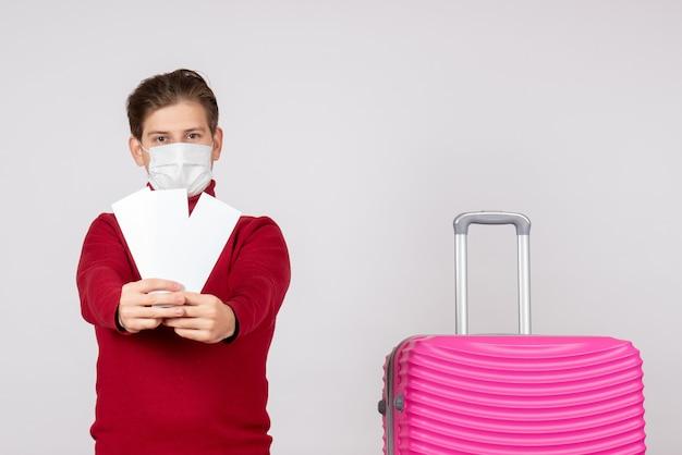 흰 벽에 비행기 티켓을 들고 마스크에 젊은 남성의 전면보기