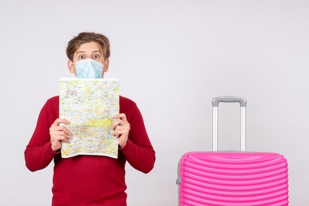 Вид спереди молодого мужчины в маске с розовой сумкой и картой на белой стене
