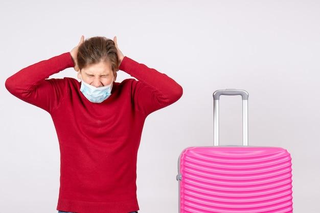 Вид спереди молодого мужчины в маске с розовой сумкой на белой стене