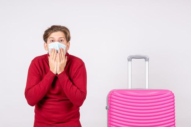 Вид спереди молодого мужчины в маске с розовой сумкой в шоке на белой стене